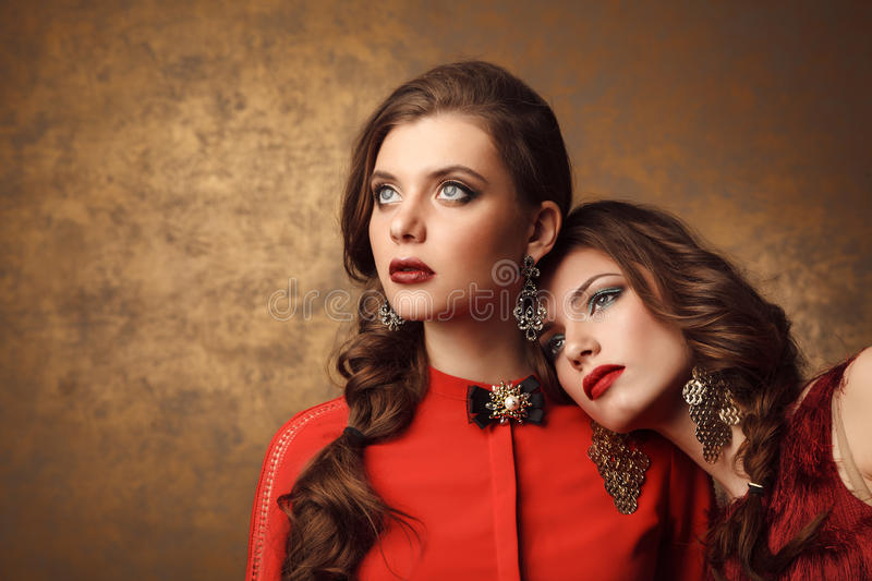 Two beautiful women in red dresses. Perfect makeup and hairstyle stock images