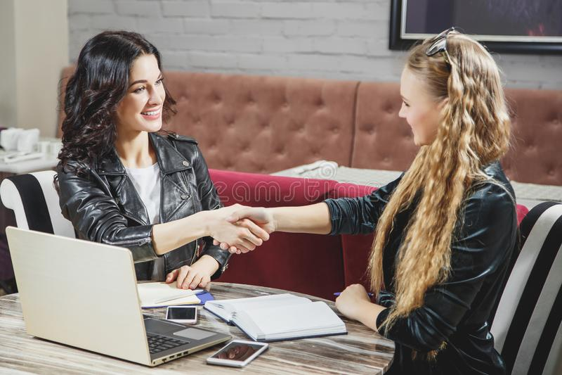 Two beautiful women shaking hands and looking at each other with smile while sitting at the business meeting. royalty free stock photography