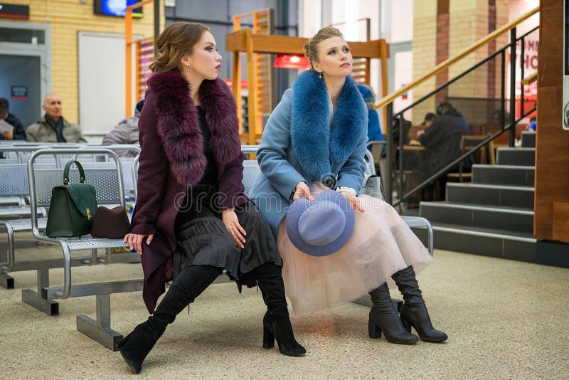 Two beautiful women at the station waiting for the train royalty free stock photo