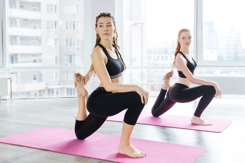 Two beautiful women stretching legs in yoga center. Two serious beautiful young women stretching legs in yoga center royalty free stock photography