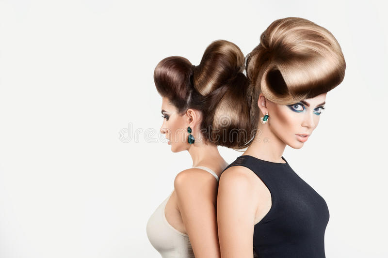 Two beautiful women in studio. Both with creative hairstyle and royalty free stock images