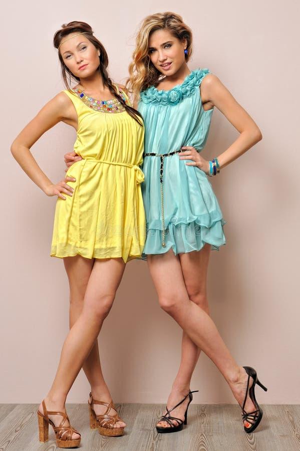 Two beautiful women in summer dresses. Studio portrait stock photos