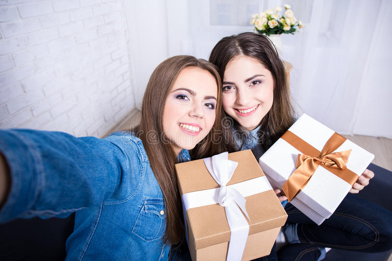 Two beautiful women taking selfie photo with presents in living stock image