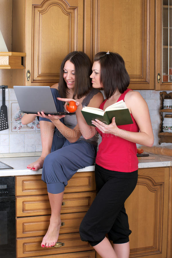 Two beautiful women trying to cook royalty free stock image