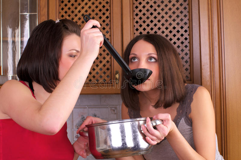 Two beautiful women trying to cook royalty free stock images
