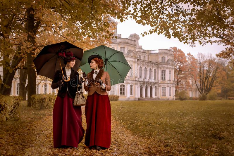 Two beautiful women with umbrellas in the park stock image