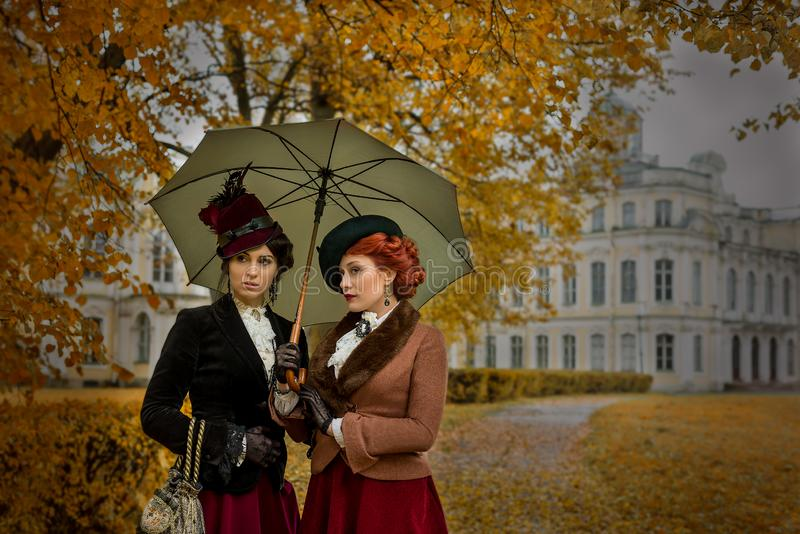 Two beautiful women with umbrellas in the park royalty free stock images