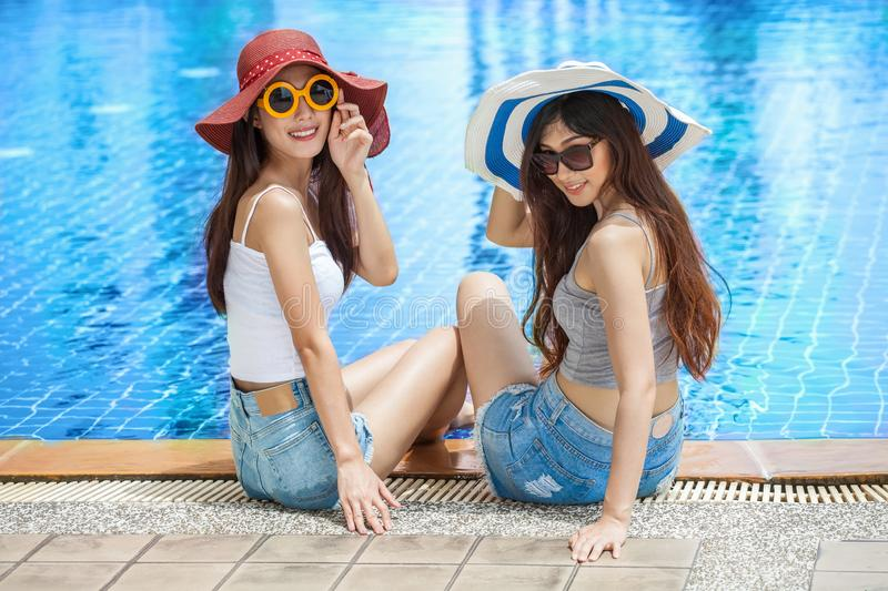 two beautiful Young Asian women in big summer hat and sunglasses sitting on the edge of the swimming pool with feet in water stock photography