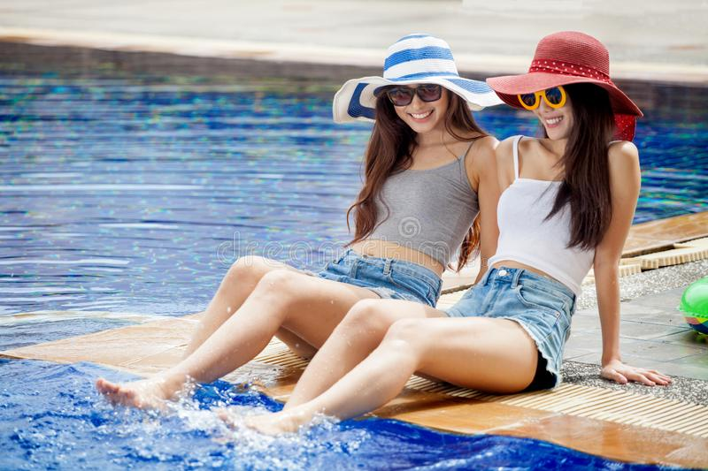 two beautiful Young Asian women in big summer hat and sunglasses sitting on the edge of the swimming pool with feet in water royalty free stock photography