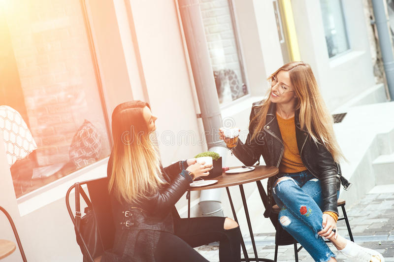 Two beautiful young blonde women drinking coffee and gossiping in nice restaurant outdoor. The weather is great and sunny for walking rest relaxing spending stock photos