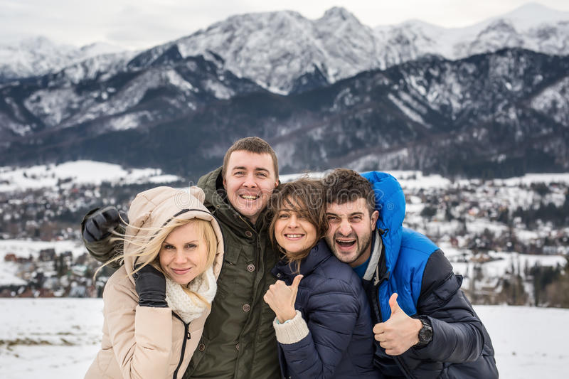 Two beautiful young couple on the background of the Polish Tatras. two women two men m. Snow-capped mountains. Winter photo. Two stock photo