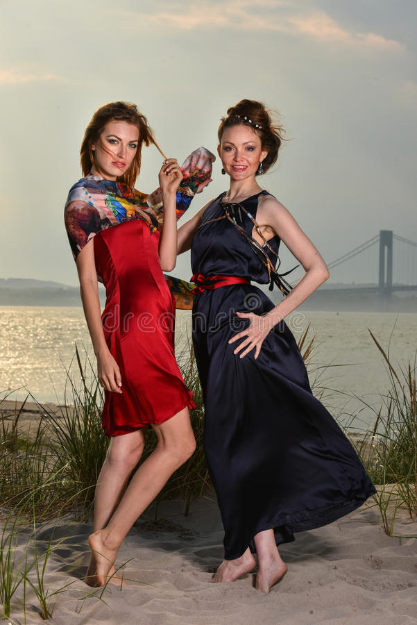 Two beautiful young fashion models posing pretty on the beach. Wearing elegant dresses stock images