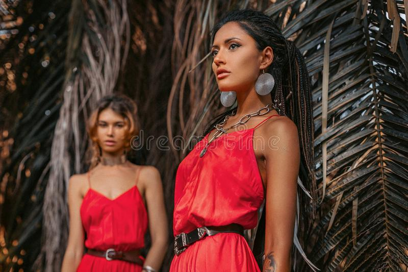 Two beautiful young fashionable models in red dresses outdoors at sunset stock photography
