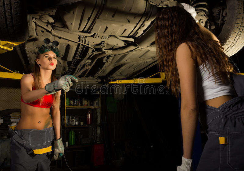 Two Beautiful young female mechanic inspecting car in auto repair shop. mechanic stock image