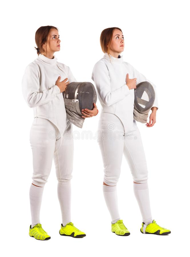 Two girls are fencers, in a uniform, holding a mask for fencing and praying. Isolated on white background. royalty free stock photography