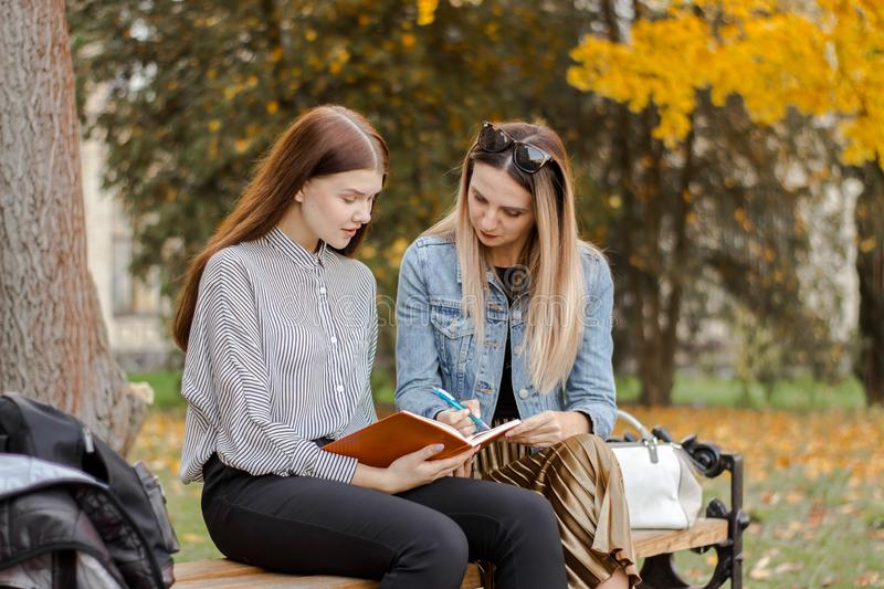 Two beautiful young girlfriends take notes while sitting on a bench in autumn park royalty free stock images
