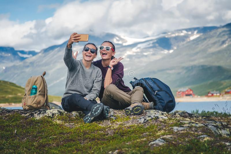Two beautiful young girlfriends travel together in Norway, adventure, hiking, lifestyle concept royalty free stock photo