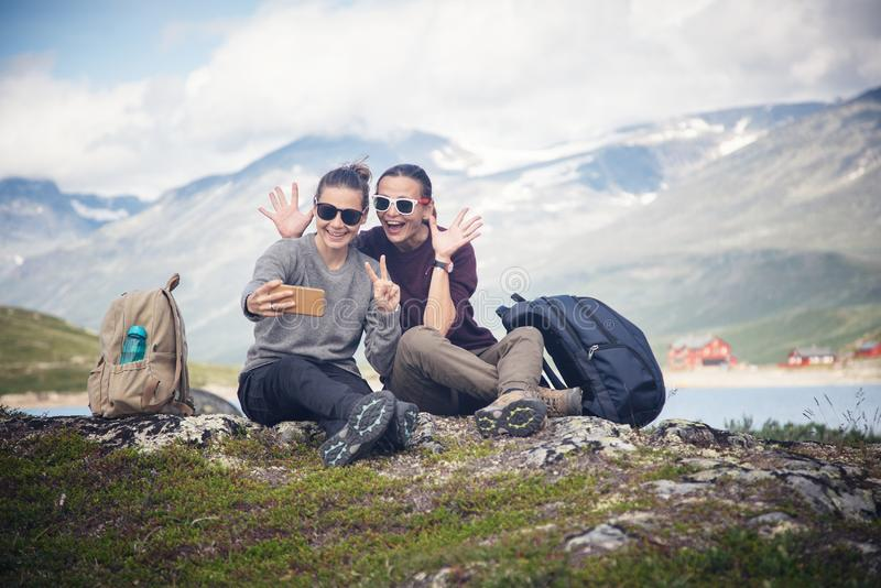 Two beautiful young girlfriends travel together in Norway, adventure, hiking, lifestyle concept royalty free stock photos