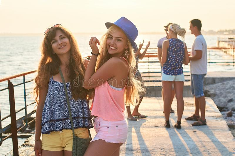 Two beautiful young girls having fun at the evening seaside with group of their friends on background royalty free stock images