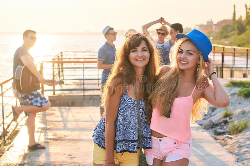 Two beautiful young girls having fun at the evening seaside with group of their friends on background stock photo