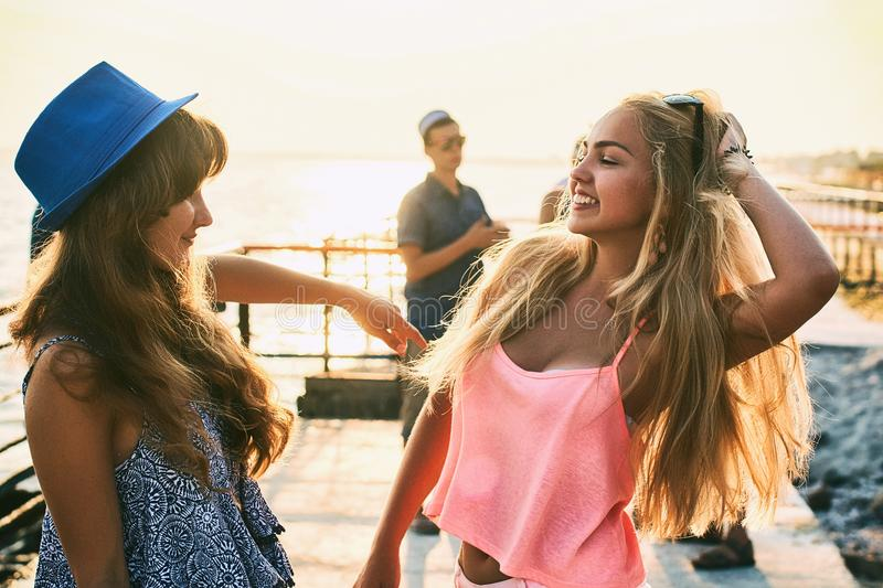 Two beautiful young girls having fun at the evening seaside with group of their friends on background stock photography