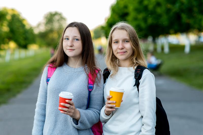 Two beautiful young girls schoolgirl. In summer outside city in fresh air. He holds hot tea and coffee in his hands royalty free stock images