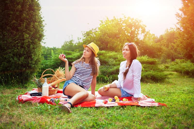 Two beautiful young girls at a picnic in the summer in the park eating apples and talking royalty free stock photo