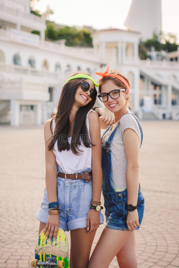 Two beautiful young girls on a skateboard in the city. royalty free stock images