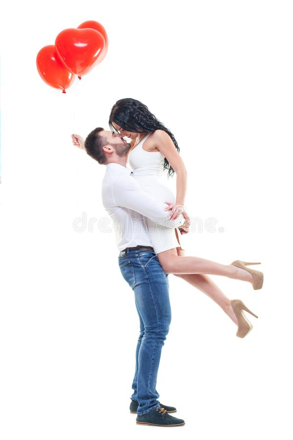 Two beautiful young people with heart-shaped balloons. hugging, the guy picked up a girl, valentines day theme. isolated. On white background stock image