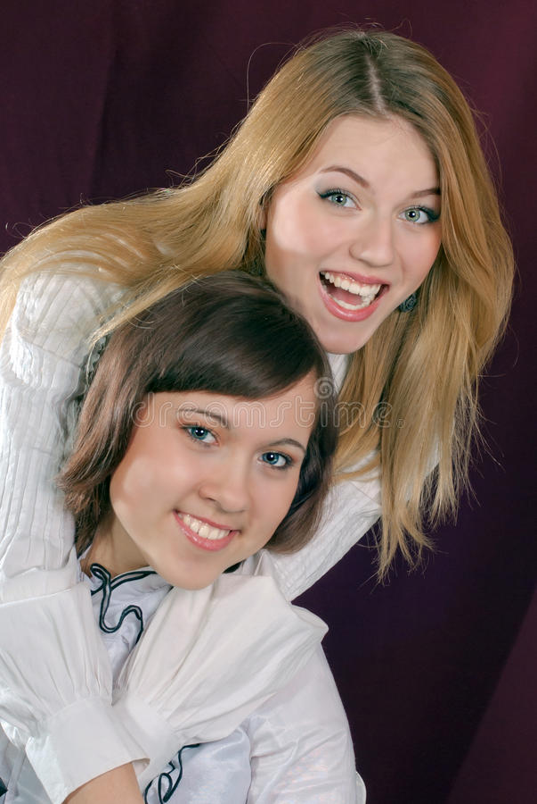 Two beautiful young woman friends smiling, hugging