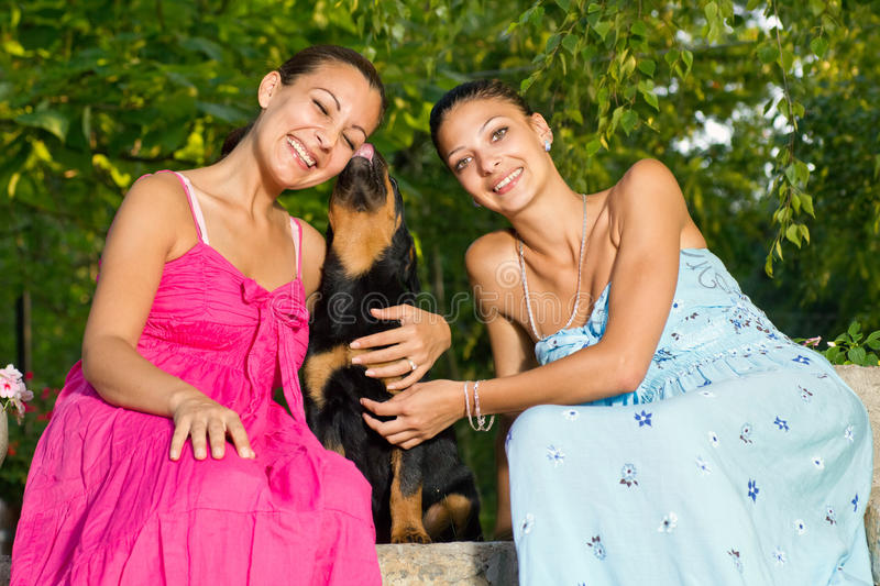 Two beautiful young woman playing with puppy in park stock photo