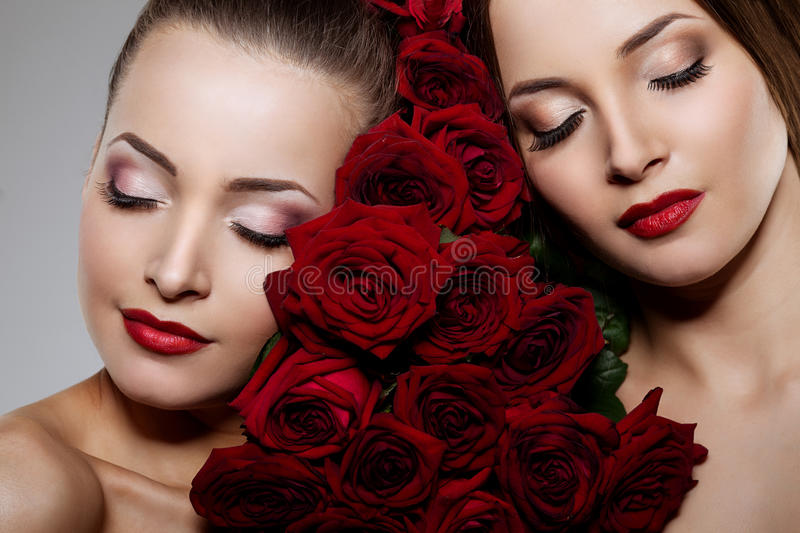 Two beautiful young women with amazing make-up in roses. Cosmetic care, makeup. Sensuality twins. Stylish attractive woman in flo. Two beautiful young women with royalty free stock image