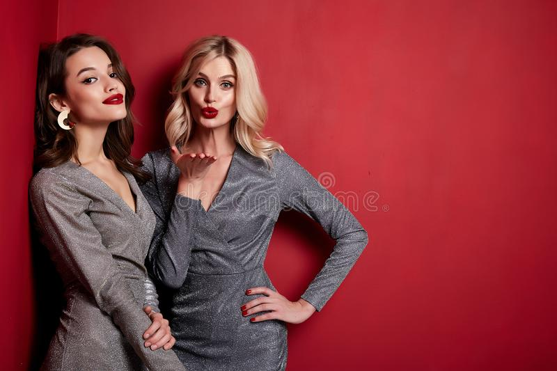 Two beautiful young woman bright evening make-up red lips long fluffy eyelashes hold gift box holiday New Year joy fun happy royalty free stock photography