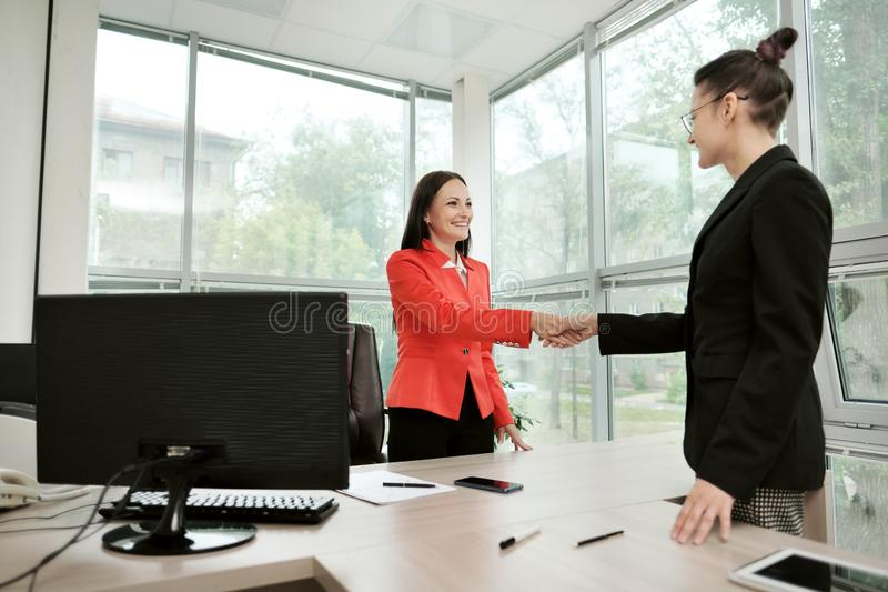 Two beautiful young women in business suits shake hands and smile. Hiring a job. Signing the agreement. Women at work. Two beautiful young women in business stock images