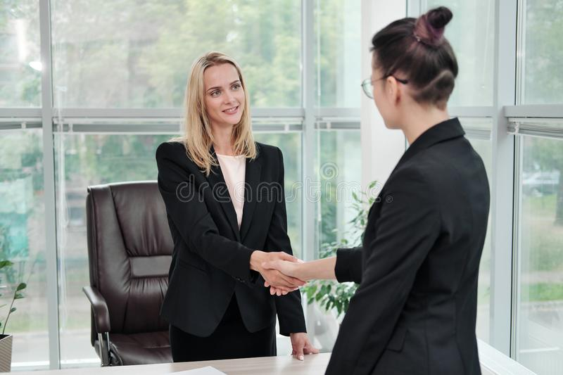 Two beautiful young women in business suits shake hands and smile. Hiring a job. Signing the agreement. Women at work. Two beautiful young women in business stock photos