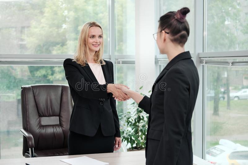 Two beautiful young women in business suits shake hands and smile. Hiring a job. Signing the agreement. Women at work. Two beautiful young women in business stock photography