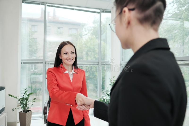 Two beautiful young women in business suits shake hands and smile. Hiring a job. Signing the agreement. Women at work. Two beautiful young women in business royalty free stock images