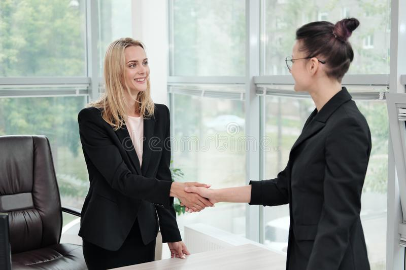 Two beautiful young women in business suits shake hands and smile. Hiring a job. Signing the agreement. Women at work. Two beautiful young women in business stock image