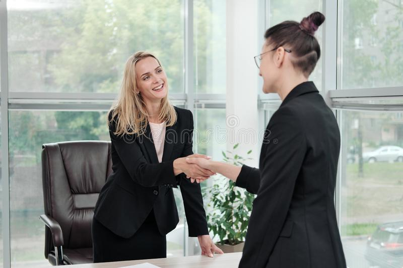 Two beautiful young women in business suits shake hands and smile. Hiring a job. Signing the agreement. Women at work. Two beautiful young women in business royalty free stock photography