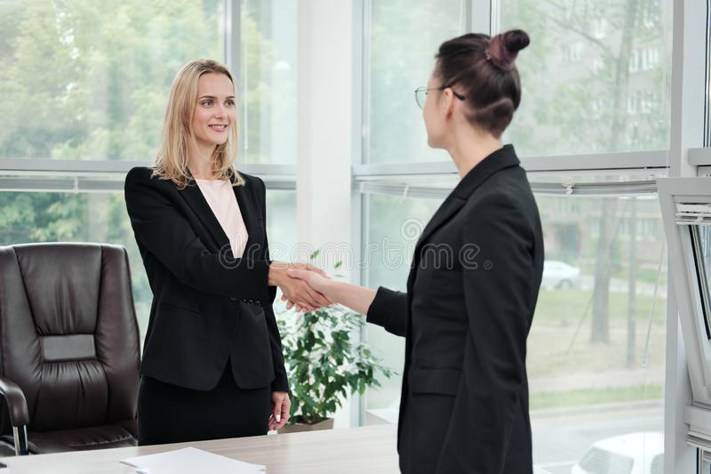 Two beautiful young women in business suits shake hands and smile. Hiring a job. Signing the agreement. Women at work. stock photos