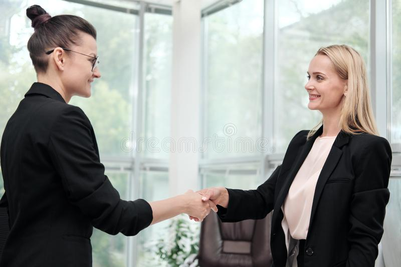 Two beautiful young women in business suits shake hands and smile. Hiring a job. Signing the agreement. Women at work. Two beautiful young women in business royalty free stock image