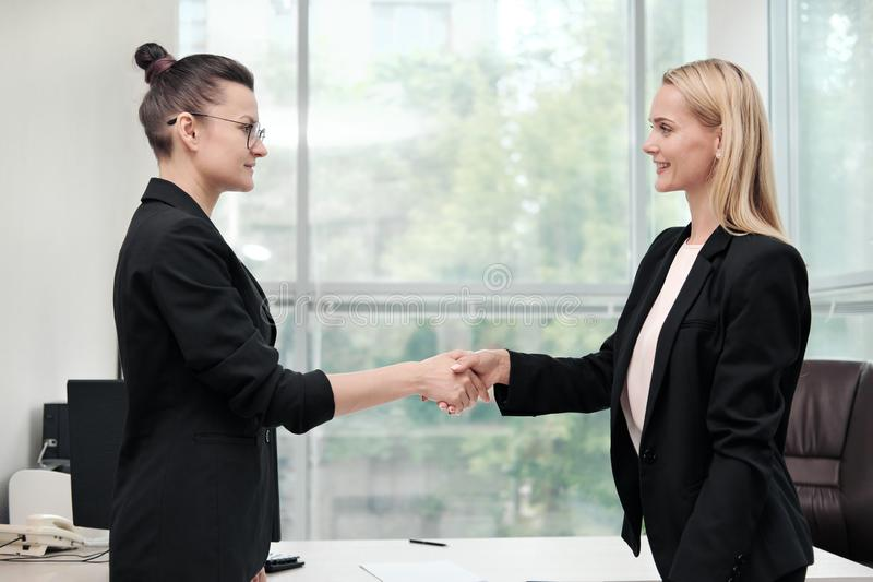 Two beautiful young women in business suits shake hands and smile. Hiring a job. Signing the agreement. Women at work. Two beautiful young women in business royalty free stock photos