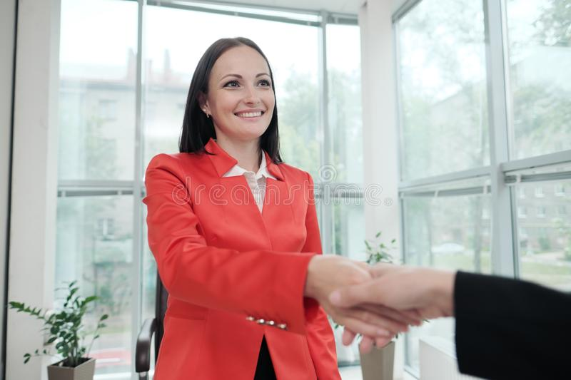 Two beautiful young women in business suits shake hands and smile. Hiring a job. Signing the agreement. Women at work. Two beautiful young woman in business stock photos