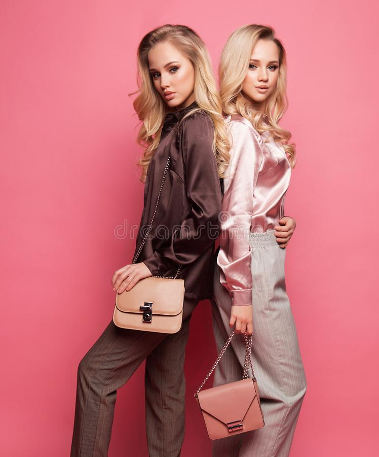 Two beautiful young women in casual clothes posing over pink background. stock images