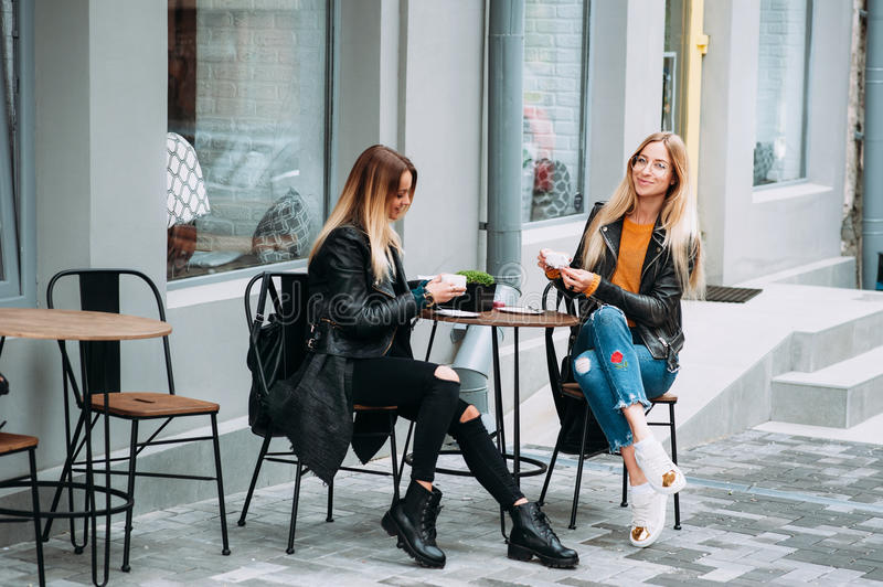 Two beautiful young women drinking tea and gossiping in nice restaurant outdoor . royalty free stock photography