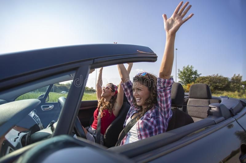 Two beautiful young women driving in a convertible with hands in the air. Daytime royalty free stock photos