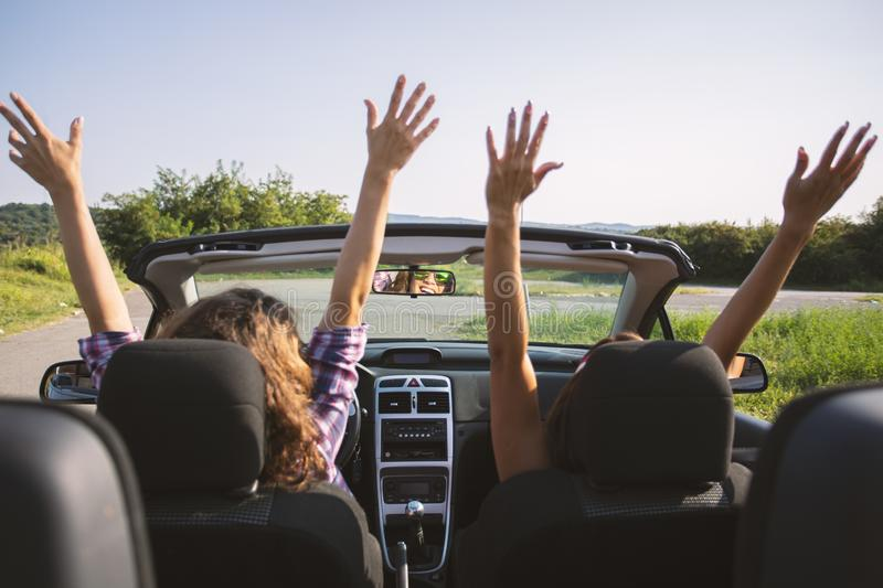 Two beautiful young women driving in a convertible with hands in the air. Daytime stock image