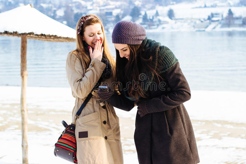 Two beautiful young women friends having fun. Looking at something funny on their mobile phone and laughing royalty free stock images