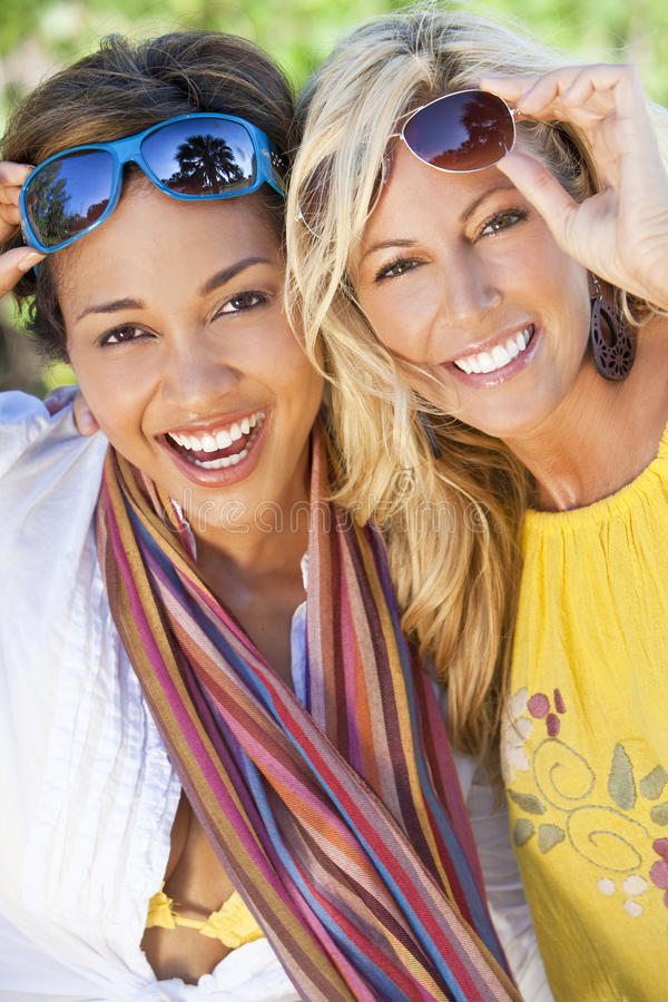 Two Beautiful Young Women Friends Laughing. Twp beautiful young women in their twenties laughing and having fun on vacation, shot in golden sunshine in a royalty free stock photo