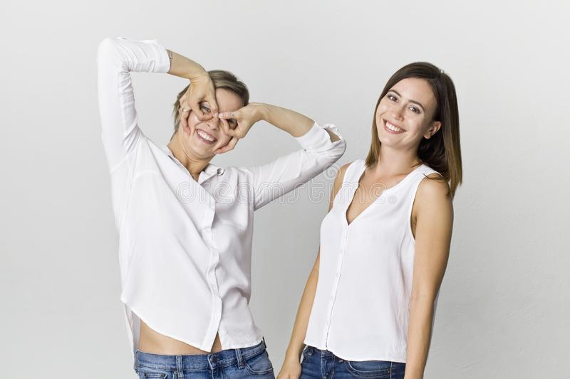 Two beautiful young women. Happy friends having fun at white background royalty free stock image